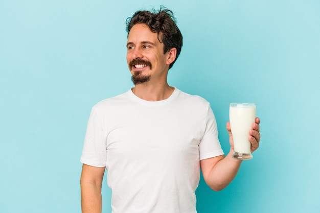Young caucasian man holding a glass of milk isolated on blue background looks aside smiling, cheerful and pleasant.