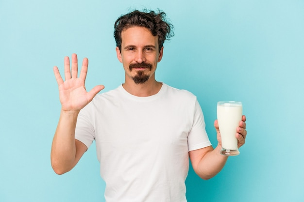 Young caucasian man holding a glass of milk isolated on blue background smiling cheerful showing number five with fingers.