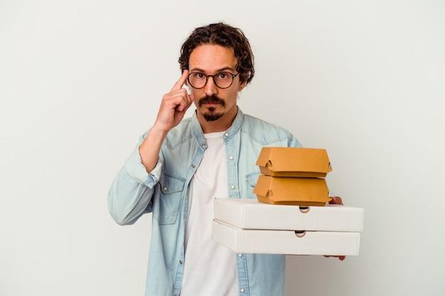 햄버거를 들고 젊은 백인 남자는 작업에 초점을 맞춘 생각, 손가락으로 사원을 가리키는 흰색 배경에 고립 된 피자.