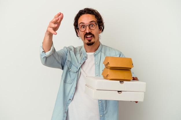 햄버거를 들고 젊은 백인 남자는 즐거운 놀라움을 받고 흰색 배경에 고립 된 피자를 흥분하고 손을 올리는.
