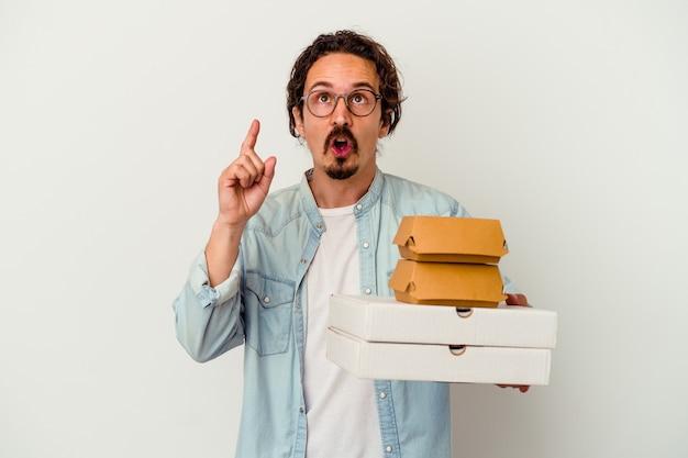 열린 된 입으로 거꾸로 가리키는 흰 벽에 고립 된 햄버거 한 피자를 들고 젊은 백인 남자.
