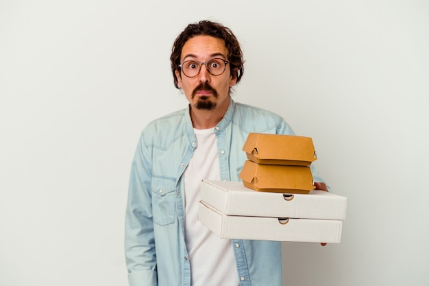 Young caucasian man holding hamburger an pizzas isolated on white wall shrugs shoulders and open eyes confused