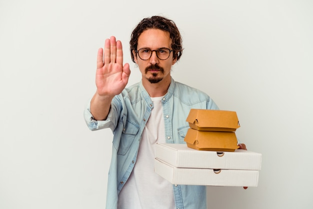 Young caucasian man holding hamburger an pizzas isolated on white wall standing with outstretched hand showing stop sign, preventing you.