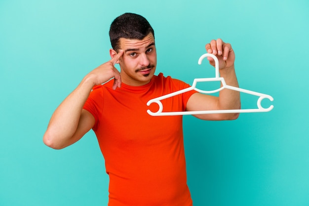 Young caucasian man holding a hanger isolated on blue pointing temple with finger, thinking, focused on a task.
