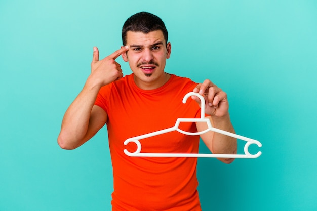 Young caucasian man holding a hanger isolated on blue showing a disappointment gesture with forefinger.