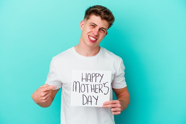 Young caucasian man holding a happy mothers day placard on blue