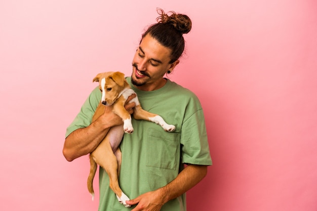Young caucasian man holding his puppy isolated on pink background