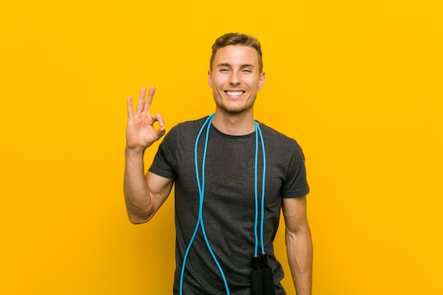 Young caucasian man holding a jump rope cheerful and confident showing ok gesture.