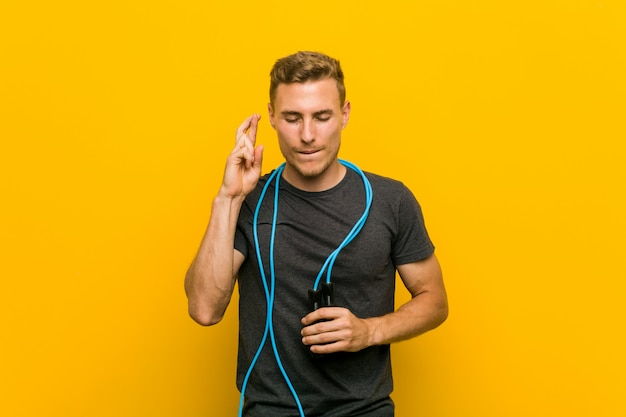 Young caucasian man holding a jump rope crossing fingers for having luck