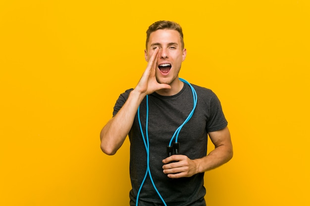Young caucasian man holding a jump rope shouting excited to front.
