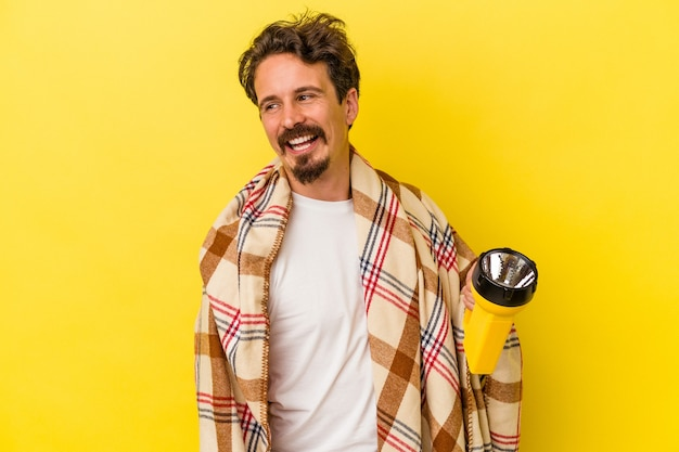 Young caucasian man holding lantern isolated on yellow background looks aside smiling, cheerful and pleasant.
