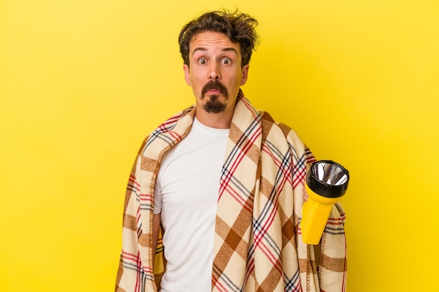 Young caucasian man holding lantern isolated on yellow background shrugs shoulders and open eyes confused.