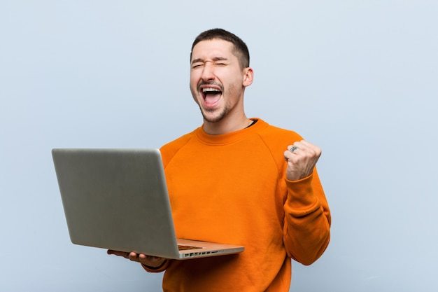 Young caucasian man holding a laptop cheering carefree and excited. victory concept.