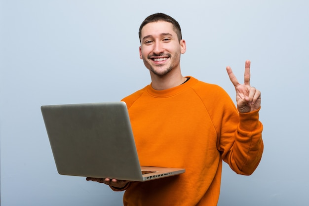 Young caucasian man holding a laptop showing number two with fingers.