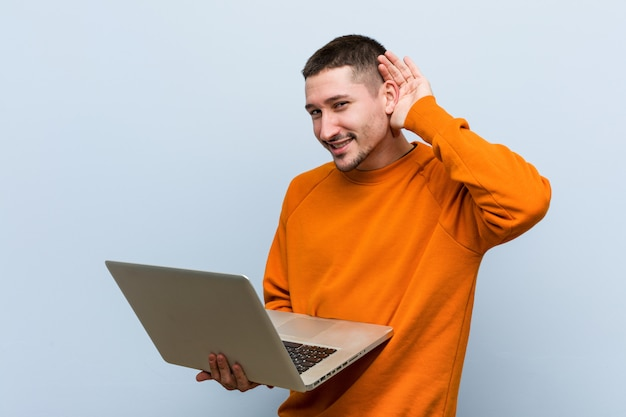 Young caucasian man holding a laptop trying to listening a gossip.