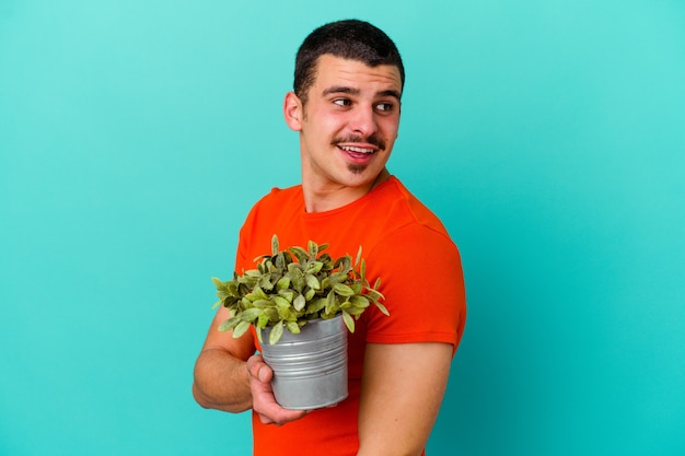 Young caucasian man holding a leaf isolated on blue background looks aside smiling, cheerful and pleasant.