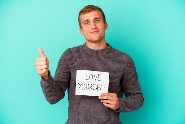 Young caucasian man holding a love yourself placard isolated on blue   background