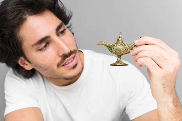 Young caucasian man holding a magic lamp on a grey wall