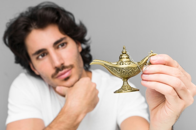 Young caucasian man holding a magic lamp isolated on a grey wall