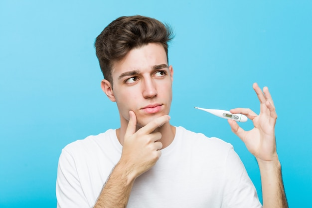 Young caucasian man holding a medical thermometer looking sideways with doubtful and skeptical expression.