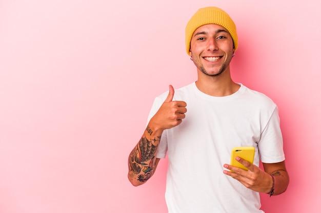 ピンクの背景に分離された携帯電話を保持している若い白人男性笑顔と親指を上げる