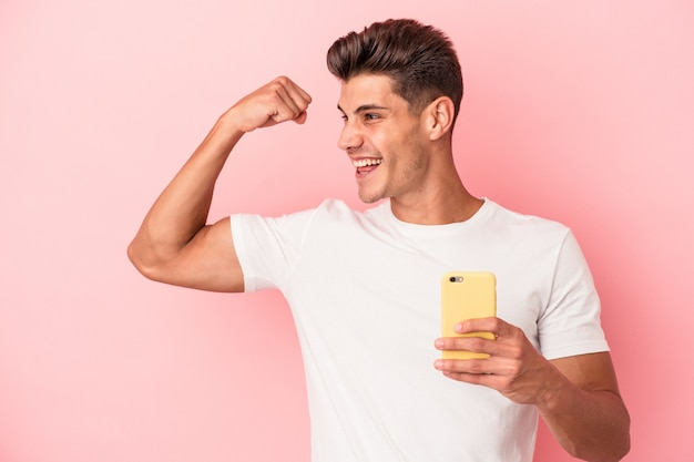 Young caucasian man holding a mobile phone isolated on pink background raising fist after a victory, winner concept.