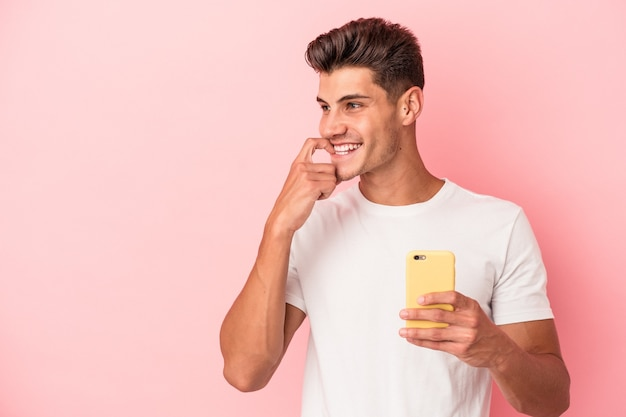 Young caucasian man holding a mobile phone isolated on pink background relaxed thinking about something looking at a copy space.