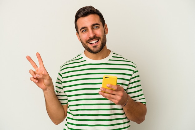 Young caucasian man holding a mobile phone isolated on white background joyful and carefree showing a peace symbol with fingers.