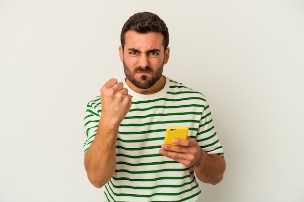 Young caucasian man holding a mobile phone isolated on white background showing fist to camera, aggressive facial expression.