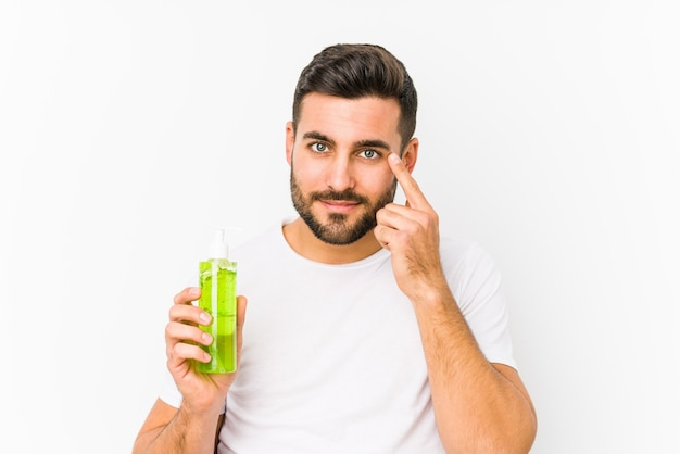 Young caucasian man holding a moisturizer with aloe vera isolated pointing his temple with finger, thinking, focused on a task.