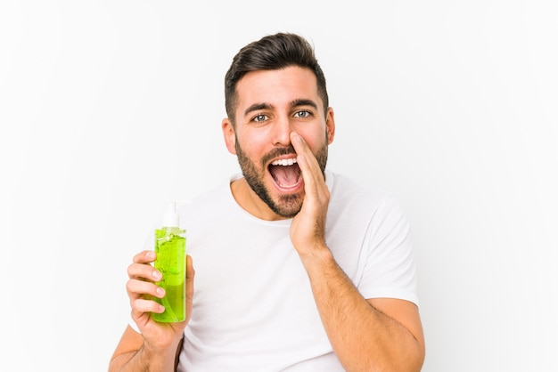 Young caucasian man holding a moisturizer with aloe vera isolated shouting excited to front.