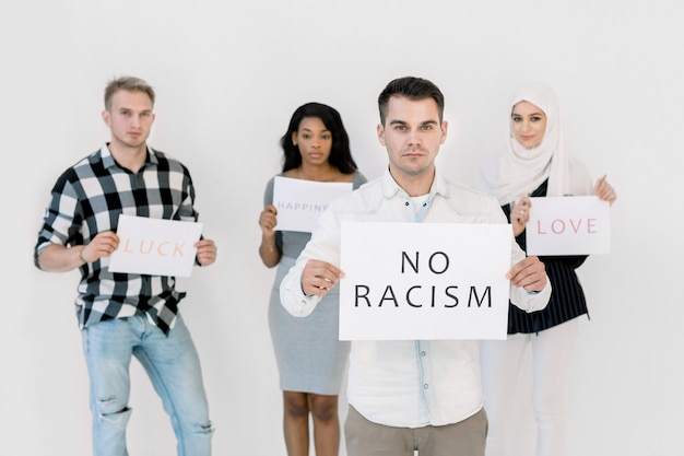 Young caucasian man holding no racism sign, three multiethnical friends activists holding social slogans, love, happiness