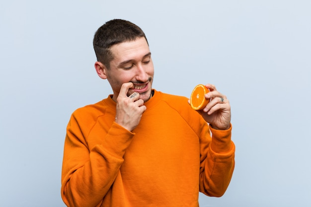 Young caucasian man holding an orange relaxed thinking about something looking at a copy space.