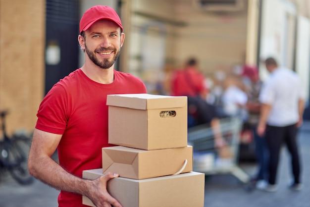 Молодой кавказский мужчина держит бумажные коробки для доставки