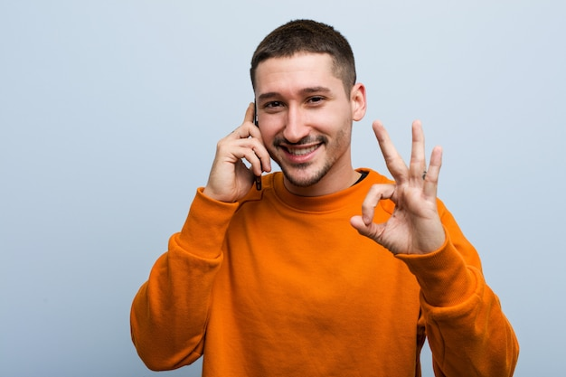 Young caucasian man holding a phone cheerful and confident showing ok gesture.