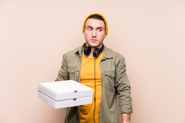 Young caucasian man holding pizzas confused, feels doubtful and unsure.