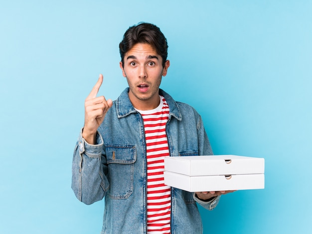 Young caucasian man holding pizzas isolated having an idea, inspiration concept.