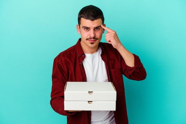 손가락으로 사원을 가리키는 파란색 배경에 고립 된 피자를 들고 젊은 백인 남자 생각, 작업에 초점을 맞춘.