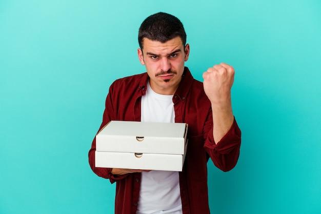 카메라, 공격적인 표정에 주먹을 보여주는 파란색 배경에 고립 된 피자를 들고 젊은 백인 남자.