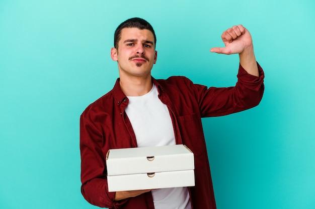 파란색 벽에 고립 된 피자를 들고 젊은 백인 남자는 자랑스럽고 자신감을 느낍니다.