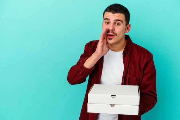 青い壁に隔離されたピザを保持している若い白人男性は、秘密の熱いブレーキングニュースを言って脇を見ています