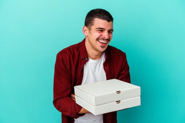 笑って楽しんで青い壁に分離されたピザを保持している若い白人男性