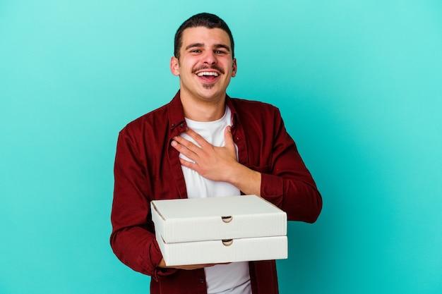 青い壁に隔離されたピザを持っている若い白人男性は、胸に手を置いて大声で笑います。