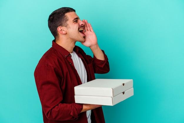 開いた口の近くで叫び、手のひらを保持している青い壁に分離されたピザを保持している若い白人男性
