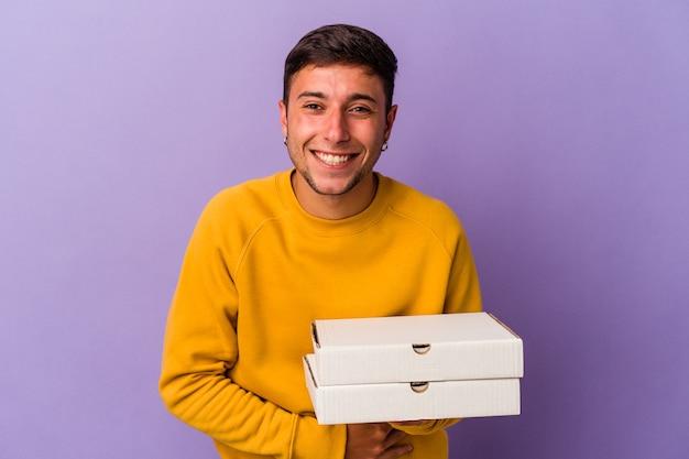 Молодой кавказский человек, держащий пиццу, изолированную на фиолетовом фоне, смеясь и весело проводя время.