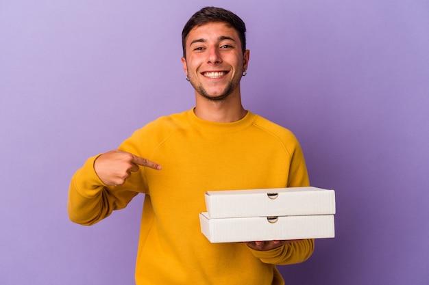 Молодой кавказский мужчина держит пиццу, изолированную на фиолетовом фоне, человек, указывая рукой на пространство для копирования рубашки, гордый и уверенный