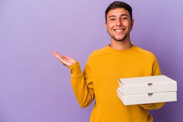 手のひらにコピースペースを示し、腰に別の手を保持している紫色の背景に分離されたピザを保持している若い白人男性。