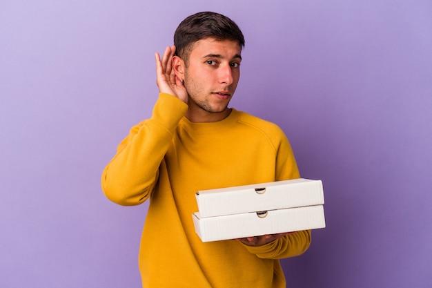 Молодой кавказский человек, держащий пиццу на фиолетовом фоне, пытается слушать сплетни.