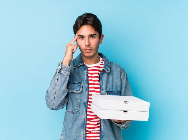 Young caucasian man holding pizzas isolated pointing temple with finger, thinking, focused on a task.