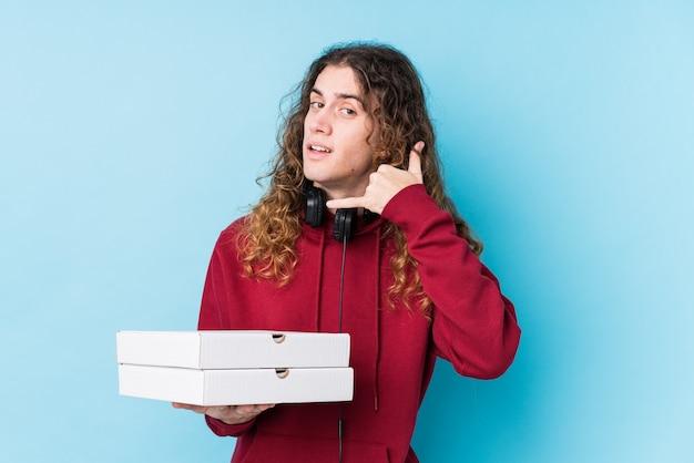 Молодой кавказский человек, держащий пиццу изолировал, показывая жест звонка мобильного телефона пальцами.